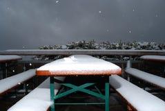 La neige tombe sur une table et des beerbanks dans une terrasse Images stock