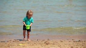 La neonata che giocano il secchio e la pala scavano sulla sabbia archivi video