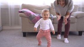 La neonata d'applauso di attimo della madre sta imparando camminare stock footage