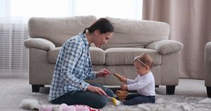 La neonata d'applauso di attimo della madre sta imparando giocare stock footage