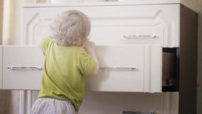 La neonata divertente prende i suoi vestiti dal cassetto dell'apprettatrice video d archivio
