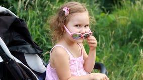 La neonata felice in occhiali da sole si siede in un passeggiatore e si rallegra stock footage