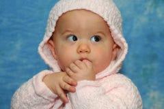La neonata impara come succhiare il suo pollice Immagine Stock