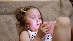 La neonata scarica l'applicazione sullo smartphone Bambino che gioca su un telefono cellulare video d archivio