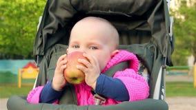 La neonata si siede in un passeggiatore di bambino e mangia una mela archivi video