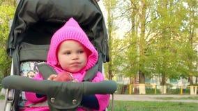 La neonata si siede in un passeggiatore di bambino e mangia una mela stock footage