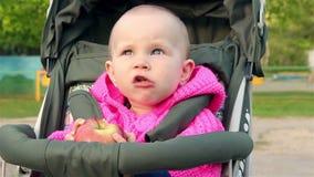 La neonata si siede in un passeggiatore di bambino e mangia una mela video d archivio