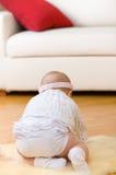 La neonata sola si siede su pelliccia al pavimento di legno duro Fotografia Stock