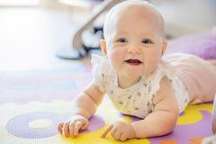 La neonata sorridente con gli occhi azzurri che giocano sul pavimento si accoppia Immagine Stock Libera da Diritti