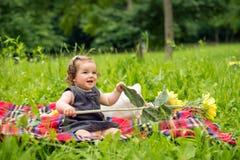 La neonata sta giocando con il girasole immagine stock