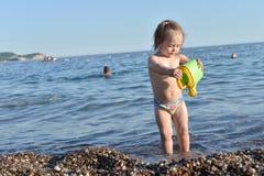 La neonata sta giocando nell'acqua immagini stock