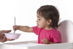 La neonata sta mangiando sola con una forcella Immagine Stock