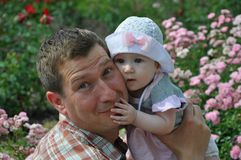 La neonata sveglia in un cappello abbraccia suo padre sorridente immagini stock libere da diritti
