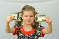 La neonata tiene in mani una banconota lacerata, dollaro, crisi bancaria Immagine Stock