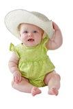La neonata in vestito verde si siede il cappello di paglia grande d'uso Fotografie Stock