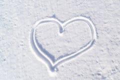 La neve bianca con annega la forma del cuore immagini stock