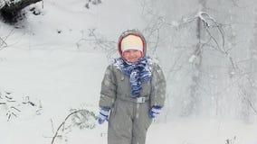 La neve cade dagli alberi sul bambino stock footage