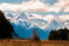La neve caped lo scape della montagna con una pianura piana Fotografia Stock