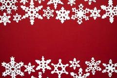 La neve di carta si sfalda sui precedenti rossi Tema di rosso di Natale Immagini Stock Libere da Diritti