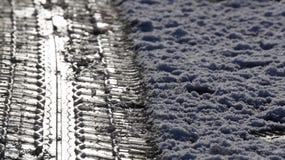 La neve grandina la strada coperta di ghiaccio con le impressioni del pneumatico fotografie stock libere da diritti