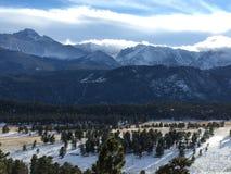 La neve ha ricoperto i picchi di montagna, le nuvole ed il cielo blu Immagine Stock