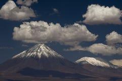 La neve ha ricoperto il vulcano con cielo blu e le nubi bianche Fotografia Stock