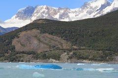 La neve ha ricoperto la montagna e l'iceberg blu in un lago Fotografia Stock