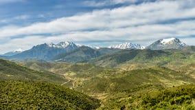 La neve ha ricoperto le montagne della Corsica con le valli verdi fertili Fotografia Stock