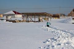 La neve ha slittato iarda nell'inverno sulla donna dell'azienda agricola rimuove il passaggio alla casa nella neve fotografie stock libere da diritti