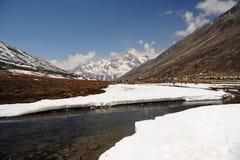 La neve Mountain View e l'acqua scorrono con cielo blu ad allo zero assoluto immagine stock libera da diritti