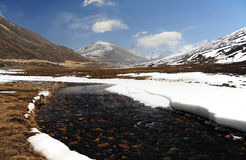 La neve Mountain View e l'acqua scorrono con cielo blu ad allo zero assoluto immagini stock