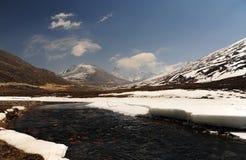 La neve Mountain View e l'acqua scorrono con cielo blu ad allo zero assoluto fotografia stock