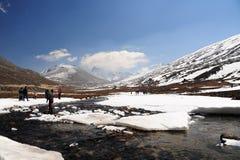 La neve Mountain View e l'acqua scorrono con cielo blu ad allo zero assoluto immagini stock libere da diritti