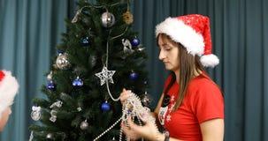 La neve nubile con uno gnomo decora un albero di Natale con le perle di Natale video d archivio