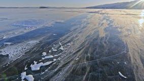 La neve sta sorvolando la superficie di ghiaccio I fiocchi di neve volano su ghiaccio del lago Baikal Il ghiaccio è molto bello c video d archivio