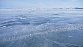 La neve sta sorvolando la superficie di ghiaccio I fiocchi di neve volano su ghiaccio del lago Baikal Il ghiaccio è molto bello c archivi video