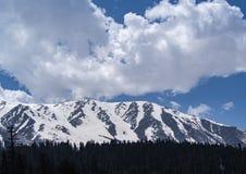 La neve sulla cima della montagna con il fondo del cielo blu immagini stock libere da diritti