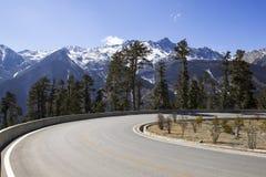 La neve torreggiante ha ricoperto le montagne che si elevano nel cielo Immagine Stock