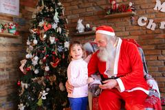 La niña abraza a Santa Claus y hace el deseo para la Navidad en coz Imagen de archivo libre de regalías