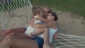 La niña abraza suavemente la mamá y a la hermana en vídeo de la cantidad de la acción de la cámara lenta de la hamaca metrajes