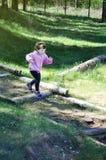 La niña adorable corre abajo de las escaleras de madera en el día soleado del bosque imagen de archivo
