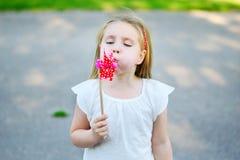 La niña adorable en día de verano sostiene el molino de viento disponible Imagen de archivo