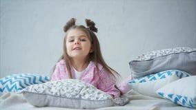 La niña adorable en pijama rosado se despertó para arriba en su cama Niño feliz almacen de video