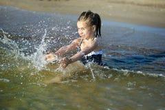 La niña adorable está salpicando y agua de mar sensacional y se está divirtiendo Foto de archivo libre de regalías