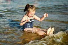 La niña adorable está salpicando y agua de mar sensacional y se está divirtiendo Fotos de archivo