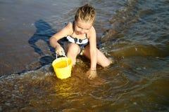 La niña adorable está salpicando y agua de mar sensacional y se está divirtiendo Imagenes de archivo
