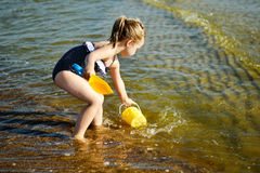 La niña adorable está salpicando y agua de mar sensacional y se está divirtiendo Imagen de archivo libre de regalías