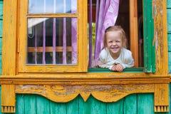 La niña adorable mira hacia fuera la ventana rural Fotografía de archivo libre de regalías