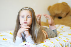 La niña adorable que miraba la cámara con sus brazos cruzó detrás de su primer principal Foto de archivo