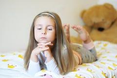 La niña adorable que miraba la cámara con sus brazos cruzó detrás de su primer principal Fotos de archivo libres de regalías